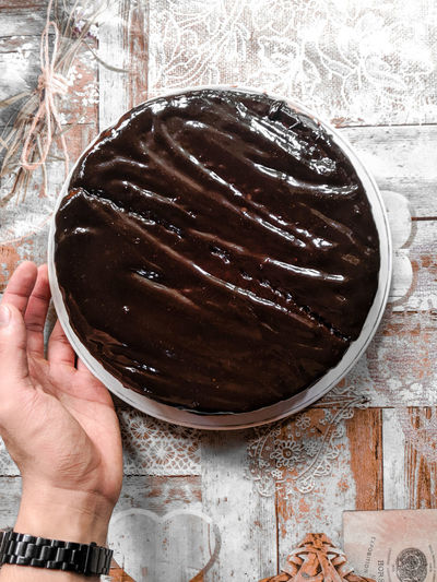 Midsection of person holding chocolate cake