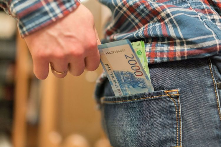 Midsection of man removing paper currency from back pocket