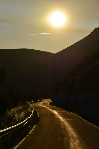Road by mountain against sky during sunset