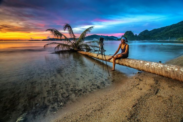 Man with tripod sitting on fallen tree at beach against sky