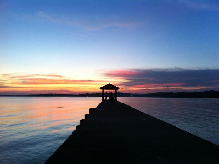 Silhouette pier on lake against sky during sunset