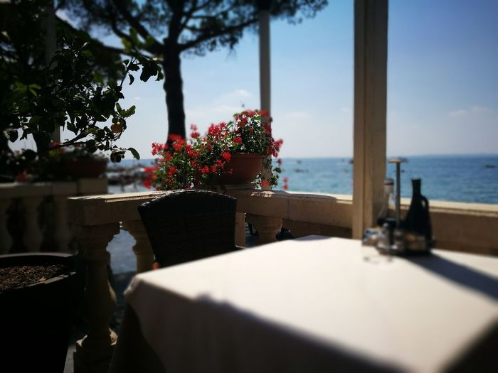 Chair and table at restaurant by lake garda