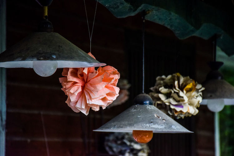 Paper Flowers Hanging By Pendant Lights In Abandoned Room