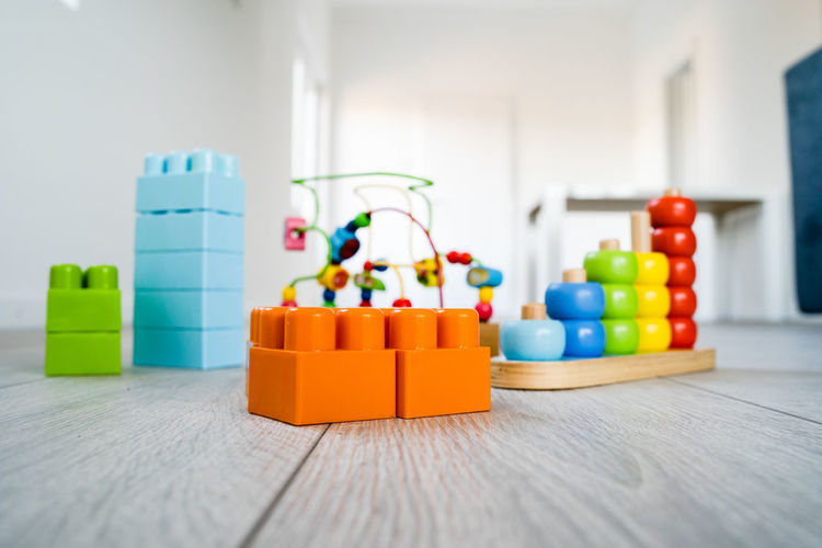Multi Colored Indoors  Still Life Table Toy No People Close-up Selective Focus Plastic Focus On Foreground Wood - Material Choice Group Of Objects Container Variation Large Group Of Objects Home Interior Orange Color In A Row Surface Level