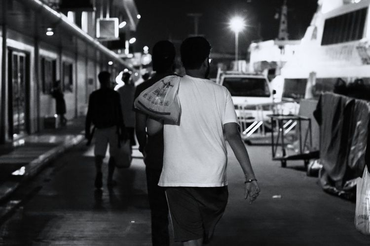 In a port city Port Fishing Harbor Harbor Harbor View Harborside Harbor Area People People Watching People Photography Night Nightlife Night Lights Night View Night Out EyeEm Best Shots EyeEm Gallery EyeEmBestPics Travel Photography Travel Destinations Vacations Eyeem4photography Blackandwhite Black And White Monochrome monochrome photography Monochrome _ Collection Men Illuminated City Walking Crowd Architecture Back Human Back Massaging Street Scene Human Body Shoulder Building