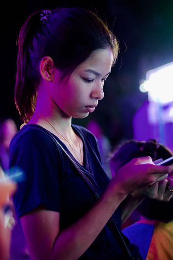 Young woman holding smart phone at night