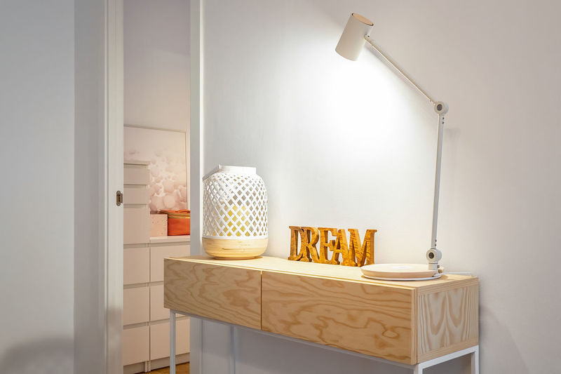 Electric lamp on table by wall at home
