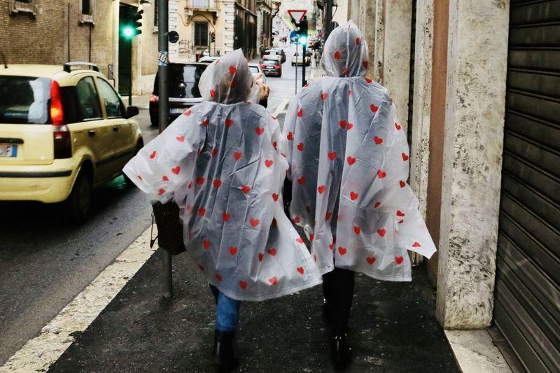 Rear view of people in raincoat walking on street