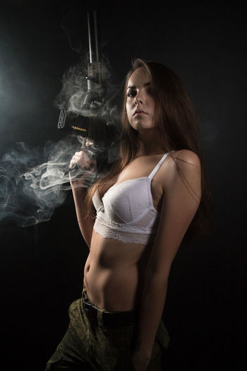 Activity Adult Beautiful Woman Beauty Black Background Dark Hair Hairstyle Indoors  Long Hair One Person Portrait Semi-dress Smoke - Physical Structure Smoking - Activity Studio Shot Three Quarter Length Women Young Adult Young Women