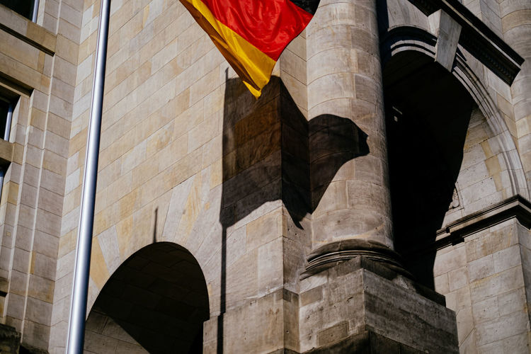 Low angle view of german flag waving against building