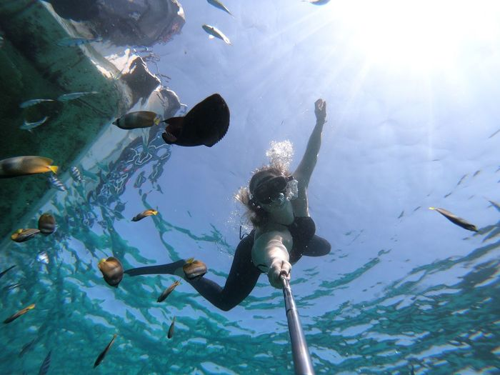 Low angle view of woman taking selfie while swimming undersea
