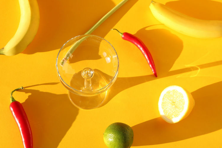 Food photography of a glas and several ingredients, including a lemon, lime, bananas, lemongras and chilies casting long shadows on a colorful yellow background Bright Colors Citrus  Cocktail Abstract Bananas Chilli Close-up Color Clash Colorful Contrast Design Food And Drink Food Photography Fruit Fruits Glass - Material Ingridients Lemon Lemongrass Lime No People Shadow Still Life Studio Shot Yellow
