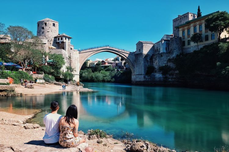 People sitting on arch bridge over water against sky