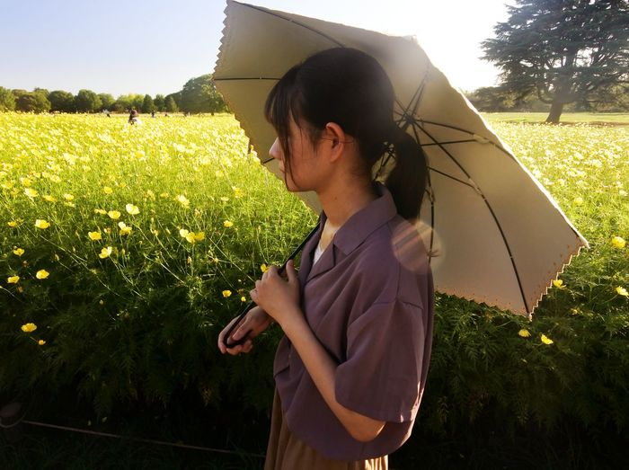 Side view of young woman standing on field