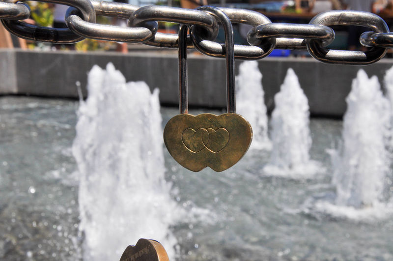 Double golden love lock hanging from chainlink fence with water feature outside the Swan Bell Tower in Perth, Western Australia. Close-up Day Engraved Fence Gold Golden Group Of Objects Hanging Heart Heart Shape Lock Locked Love Love Locks Metal Outdoors Padlock Perth Romantic Swan Bell Tower Symbolic  Water Water Feature Water Fountain Western Australia