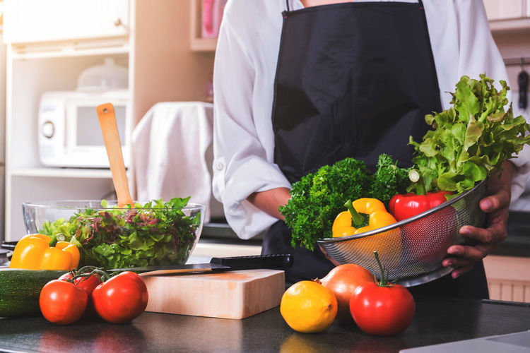 Midsection of chef holding vegetables on kitchen counter at home