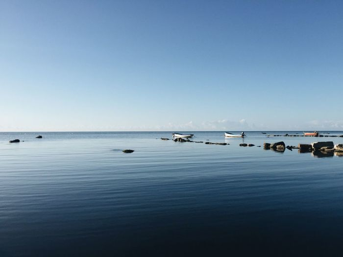 Boats In Calm Sea Against Clear Sky