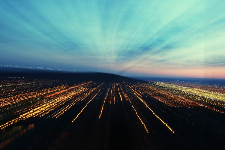 Aerial view of illuminated road against sky at night