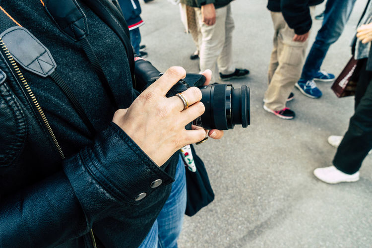 Midsection Of Woman Holding Digital Camera While Standing On Street