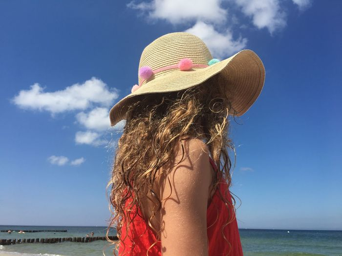 Woman wearing hat at beach against sky