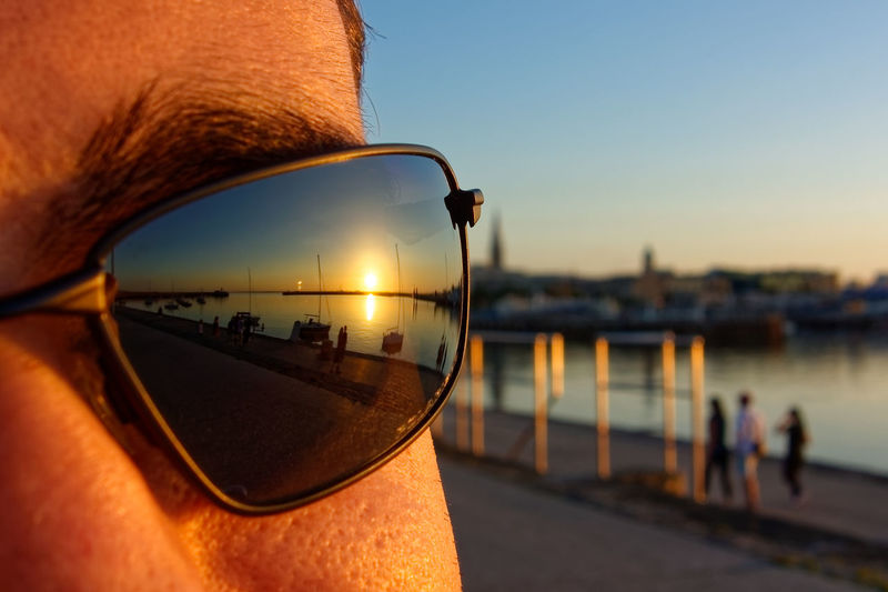 Close-up of man with sunglasses against sky during sunset