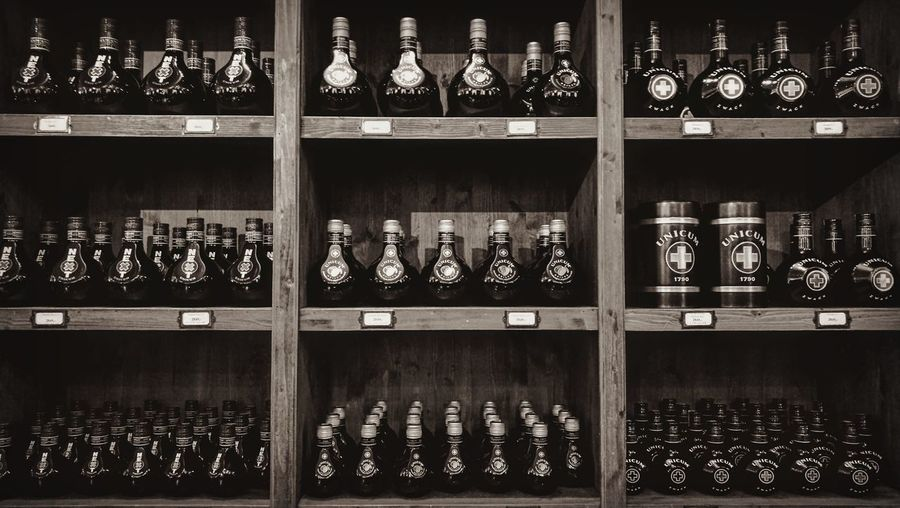 Unicum bottles Shelf Bottle Alcohol Drink Indoors  Large Group Of Objects No People Day Wooden Shelfs Unicum Unicum Plum Alcoholic Drink Alcohol Bottles Alcoholic  Alcoholic Beverages Bottles Collection Blackandwhite Black And White Black & White Blackandwhite Photography Round Round Shape Cap Factory Black And White Friday Visual Creativity The Still Life Photographer - 2018 EyeEm Awards