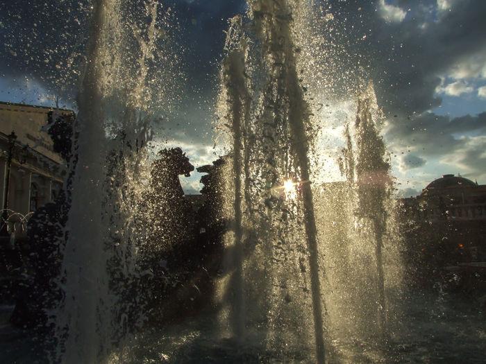Wet glass window in city against sky