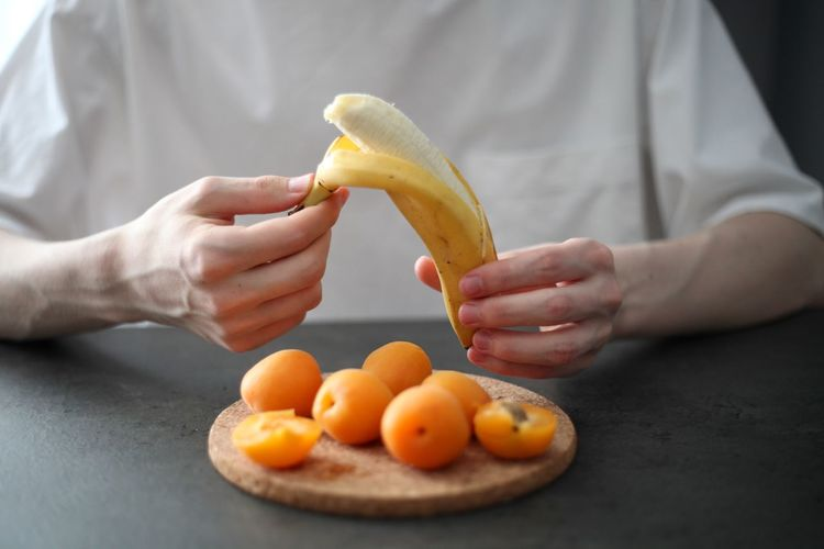 Midsection of man holding orange on table