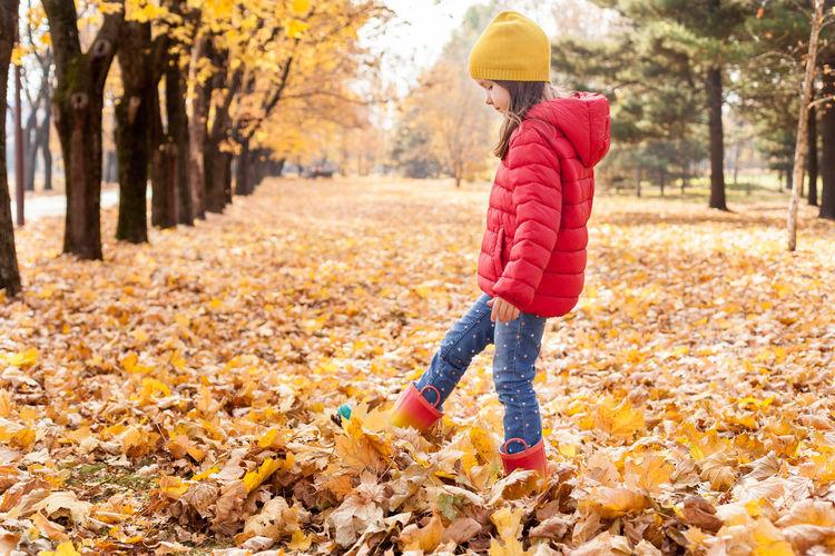 Full length of girl standing on leaves during autumn