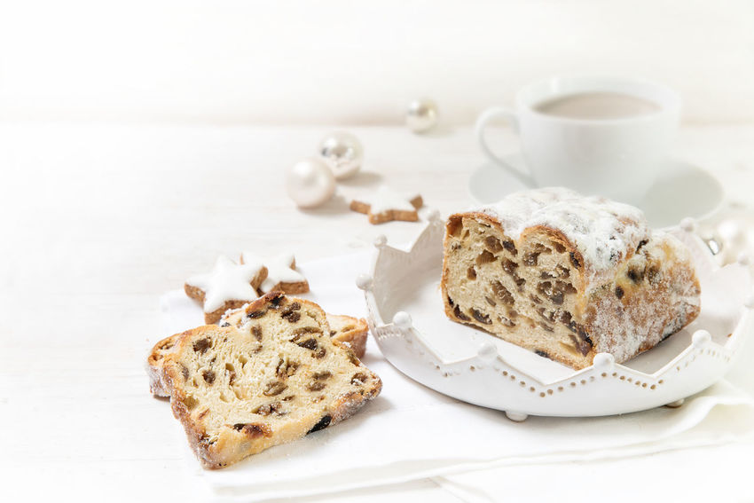 criststollen, typical german christmas cake with raisins and fruits, next to a cup of coffee, cinnamon stars and baubles on a white wooden background with copy space Advent Christmas Sugar Baking Cake Christstollen Coffee Cup Day Decoration Food Food And Drink Freshness Indoors  No People Plate Ready-to-eat Sweet Table White