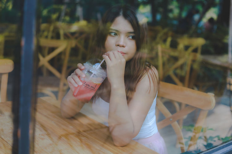Portrait of a young woman drinking drink