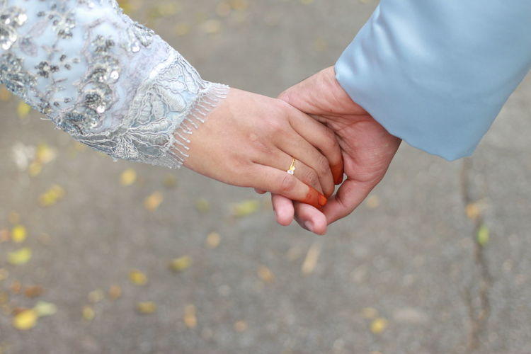 Cropped Hand Of Groom Holding Bride Hand