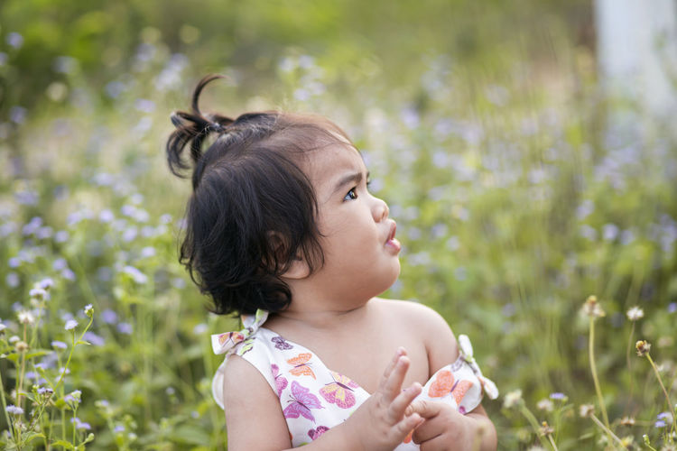 Portrait of girl looking away while standing against plants
