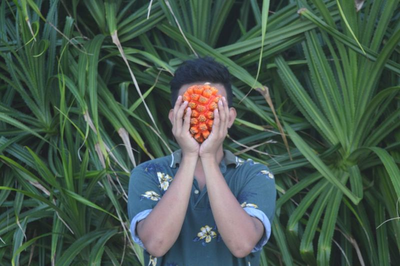 Man Holding Fruit In Front Of Face Against Plants