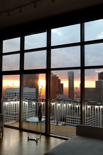 Buildings in city against sky during sunset seen through window