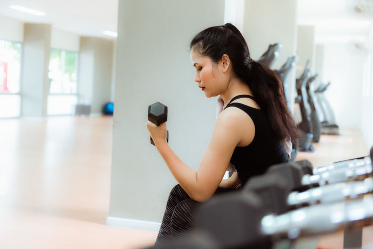 Side View Of Woman Holding Dumbbell While Exercising In Gym