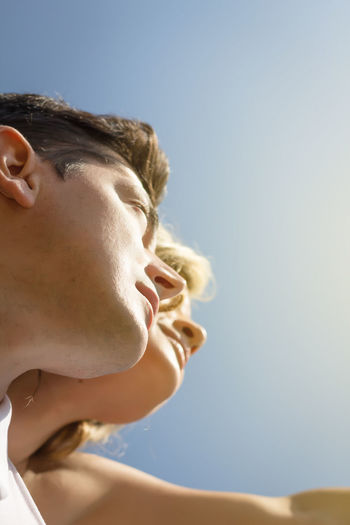 Close-up portrait of young woman against clear sky