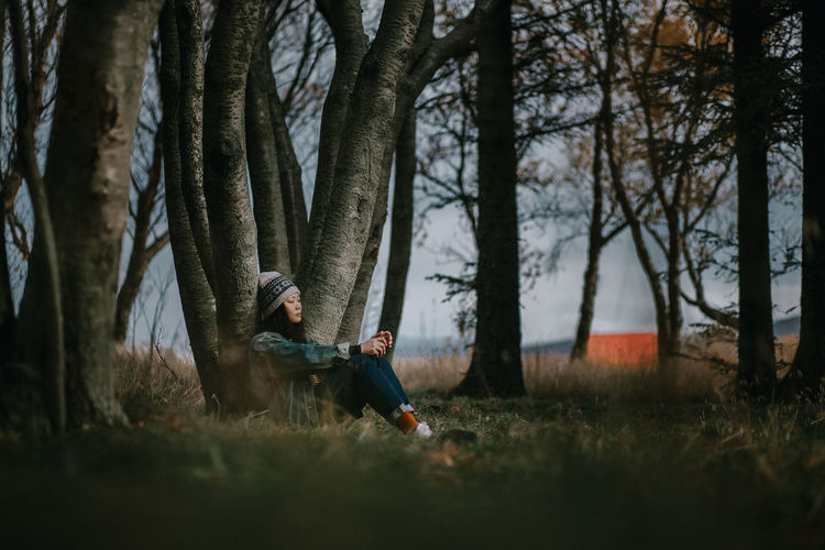 Woman sitting on land against tree trunk in forest