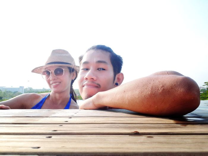 Portrait of couple resting on boardwalk in lake against sky