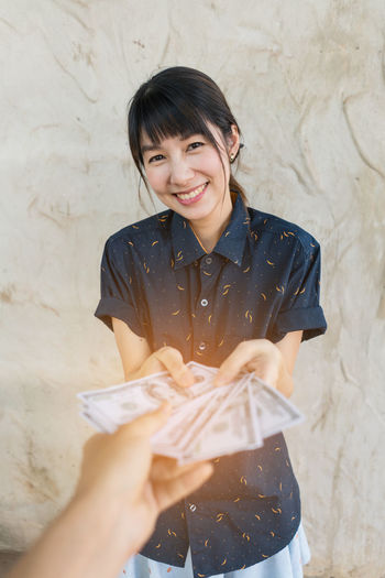 Happy girl holding money. Happy People Jidpipat_Photo Bangs Banknote Casual Clothing Emotion Front View Hairstyle Happiness Holding Indoors  Leisure Activity Lifestyles Looking At Camera Money One Person Portrait Real People Smiling Standing Three Quarter Length Waist Up Wall - Building Feature Women Young Adult EyeEmNewHere