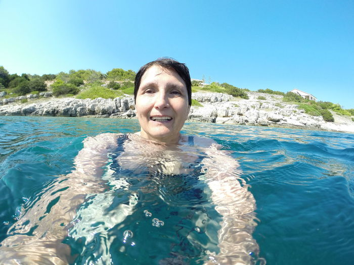 Portrait Of Senior Woman Swimming In Sea Against Clear Blue Sky