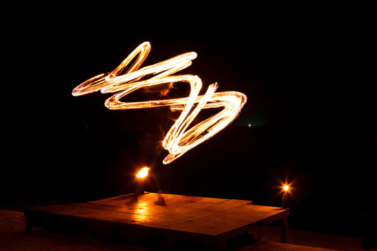 Street artist fire juggling performance. Light painting and long exposure picture to form trails. Phi Phi Island, Thailand. Artist Light Painting Show Thai Thailand Burning Fire Fire Shadows Juggler Juggling Long Exposure Motion Motion Capture Motion Photography Night Performance Performing Arts Event Phi Phi Island Spectacle Street Art Street Performer