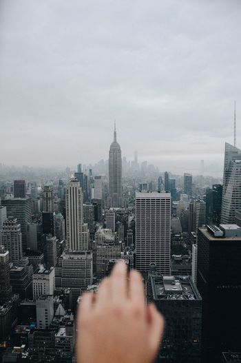 Close-up of hand over cityscape against cloudy sky