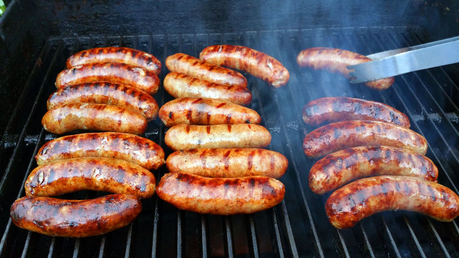 Sausages or brats cooking on a grill