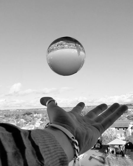 Cropped hand throwing crystal ball against sky