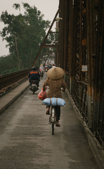 Lonely woman on bicycle on Red River Brdige in Ho Noi in the early morning. Architecture Asian Style Conical Hat Bicycle Bridge - Man Made Structure Building Exterior Built Structure Cycling Day Full Length Land Vehicle Leisure Activity Lifestyles Men Mode Of Transport One Person Outdoors Real People Rear View Riding Road The Way Forward Transportation Tree Walking Women First Eyeem Photo
