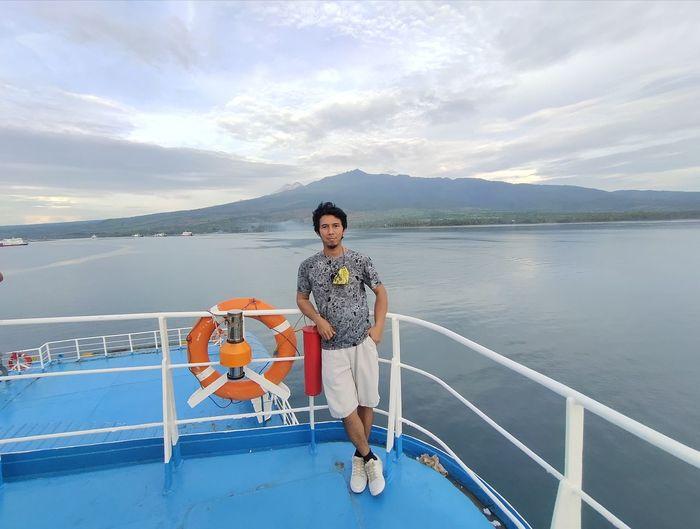 Full length of man on railing against sea