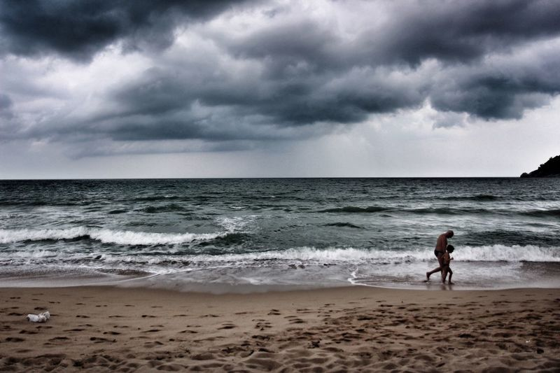 A grandfather and grandson walk along the Beach in as a Storm Cloud rolls in Beachphotography Stormy Weather Family Time Rainy Days Walking The Great Outdoors With Adobe
