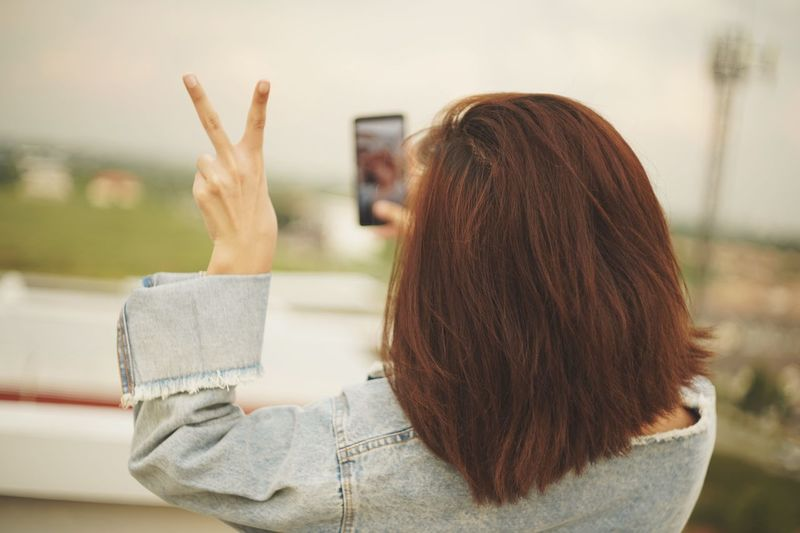 Woman gesturing peace sign while taking selfie
