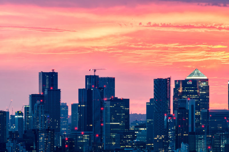 Illuminated buildings against sky during sunset